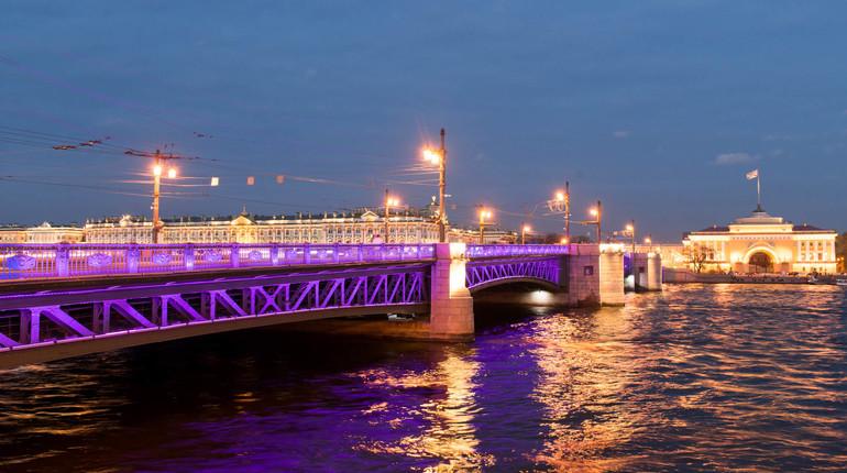 В эту субботу, 19 мая, петербуржцы увидят необычное зрелище - фиолетовый Дворцовый мост. Вместе с самой известной переправой в Петербурге в новый цвет впервые окрасятся здания МГУ и Останкинской телебашни.