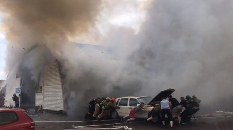Автомобили спасают всем миром из пожара на СТО в центре Петербурга. По словам очевидцев, одну из машин спасателям помогли оттаскивать прохожие.