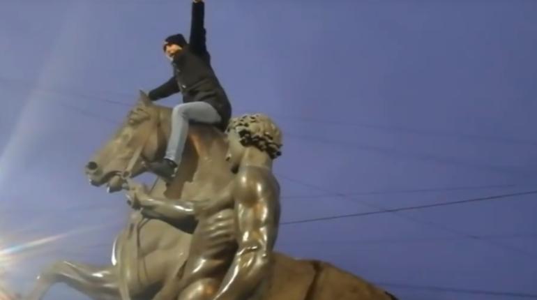 Неизвестный мужчина залез на статую коня на Аничковом мосту вечером в воскресенье. Прохожие пытались вразумить хулигана, который мог испортить скульптуру.