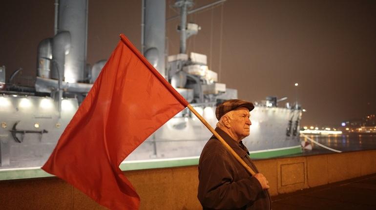 Сторонники КПРФ приближаются к «Авроре», чтобы возложить цветы. Несмотря на то, что акция несогласована, в толпе развиваются красные флаги.