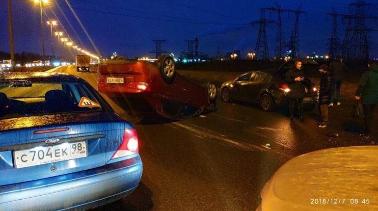 Автомобиль марки KIA Cerano перевернулся на Софийской улице утром 7 декабря. Об этом сообщили очевидцы происшествия в социальных сетях.