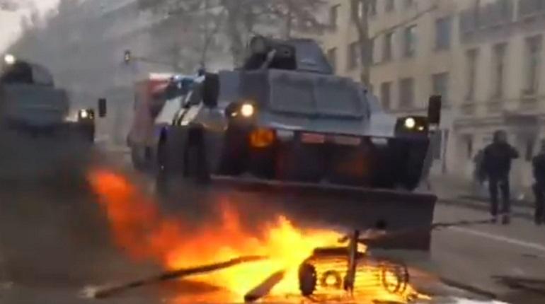 Во Франции продолжаются акции протестов «желтых жилетов». Люди, протестующие, в том числе против повышения цен на бензин, жгут машины, строят баррикады и забрасывают полицейских дымовыми шашками. В охваченный беспорядками Париж вошла бронетехника.
